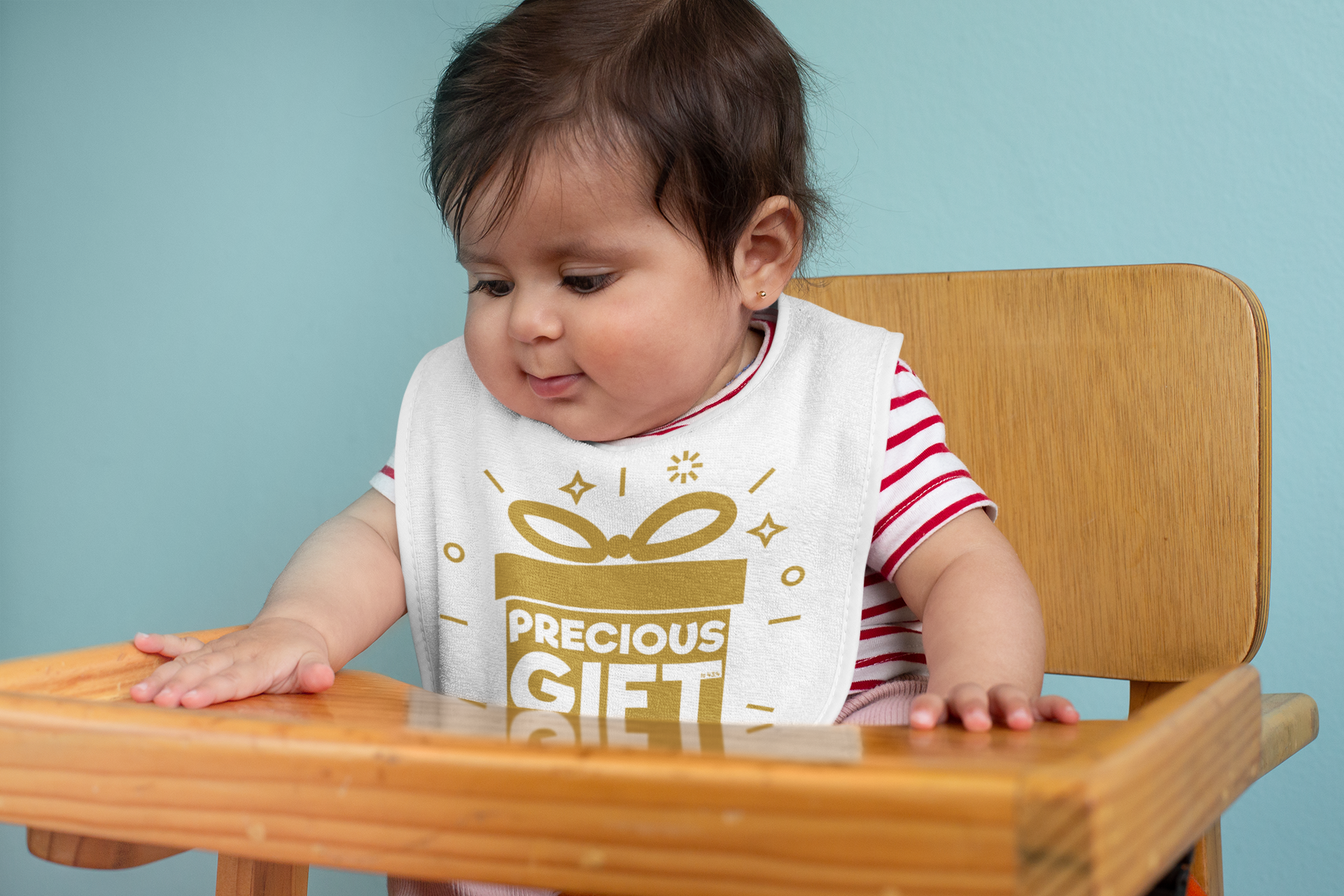 Baby wearing precious gift bib while sitting in high chair